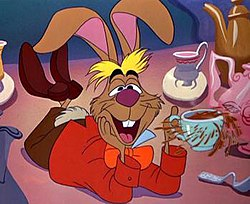 l1=A brown hare with blond bangs is laying on a table with a teacup in hi hand with tea spilling out of it.