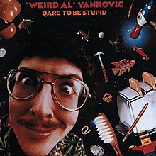 "The cover for Dare to Be Stupid features ""Weird Al"" Yankovic's face against a backdrop of space. Scattered around his head are various items, such as a fish, a toaster, a toothbrush, and a hammer."