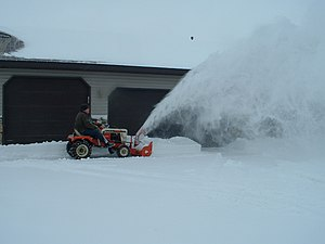 Single-stage Simplicity snow thrower in use on...