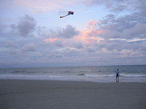A man flying a kite on the beach, a good locat...