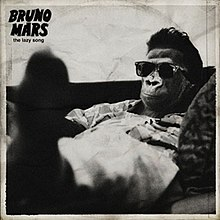 "A greyscale illustration of a chimpanzee wearing a dress shirt, pants, and sunglasses. The animal is seen reclining, with his or her feet outstretched and in the foreground. In black, the words ""The Lazy Song"" appear in minuscule below the words ""Bruno Mars"" in majuscule font."