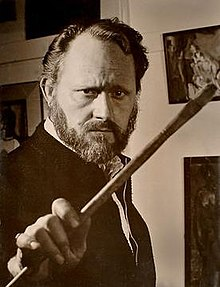 Irv Docktor in his studio in the 1960s, brandishing a paintbrush.