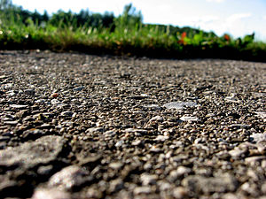 Picture of pavement with grass in the background.