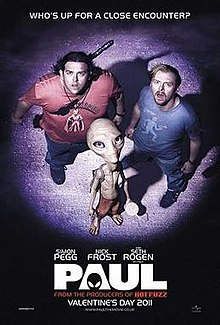 Two men and a small grey alien lit up by an spotlight