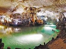 Gua cerah diterangi dilalui oleh badan bawah tanah zamrud berwarna cerah air mengelilingi berbagai speleothems di latar belakang