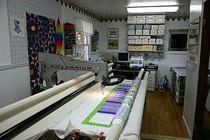 Longarm quilting machine with a quilt on the frame