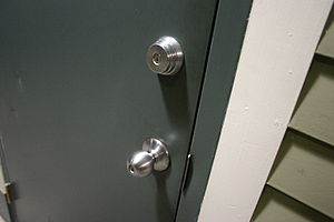 Door with two locks, one in the door knob and ...