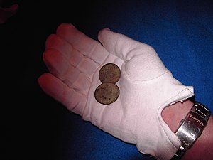 image of a curator holding ancient coins