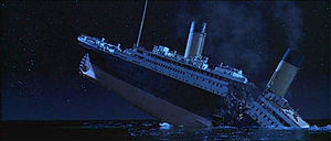 The Titanic about to sink into the ocean, with the ship breaking into two parts and with smoke still coming out of the funnels.