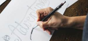 woman designing a logo with a pen and paper graphic design