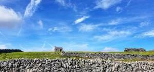 wide shot of barren area in rural ireland with a stoned wall and house photography production