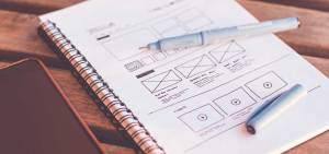 notepad with a wireframe for a website drawn on the open page web design