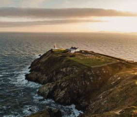 drone aerial photography production of coastal Ireland with a lighthouse