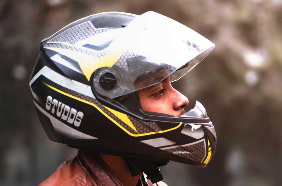 Un homme porte un casque intégral de style moto, qui est plus sûr à haute vitesse mais réduit la vision périphérique.