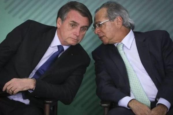 jair Bolsonaro e Paulo Guedes conversam ao pé do ouvido