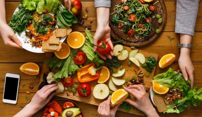 Hands with fruits, greens and vegetables