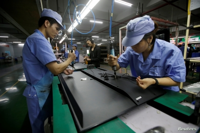 Employees work on the production line of a television factory under Zhaochi Group in Shenzhen, China August 8, 2019. Picture taken August 8, 2019. REUTERS/Jason Lee
