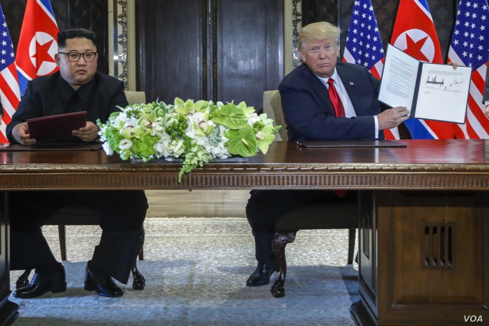 U.S. President Donald Trump holds up the document that he and North Korea leader Kim Jong Un had signed at the Capella resort on Sentosa Island, June 12, 2018, in Singapore. The most tangible outcome of their summit appeared to be a commitment to rec