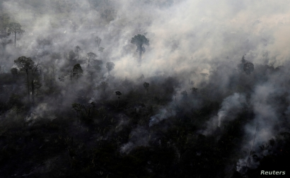 FILE - An aerial view shows smoke from a burning tract of Amazon jungle as it is cleared by loggers and farmers near Porto Velho, Brazil, Aug. 29, 2019.