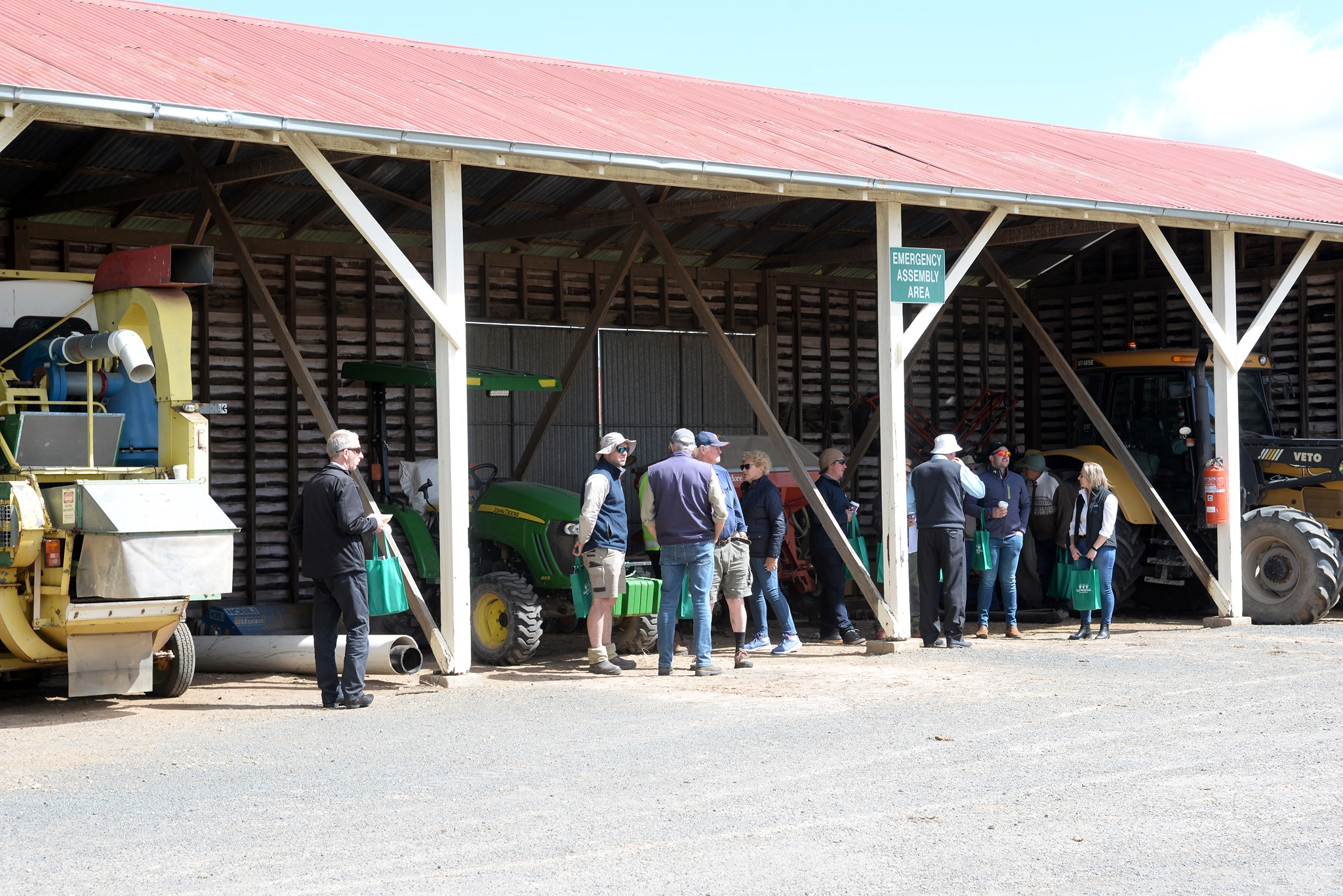Group of people assembled by a machinery shed