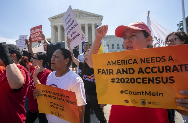 Demonstrators are seen at the Supreme Court as justices deliberate on a census case involving an attempt by the Trump administration to include a citizenship question in the 2020 census, on Capitol Hill in Washington, June 27, 2019.