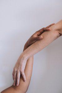 crop hands of anonymous multiethnic couple touching hands in light studio