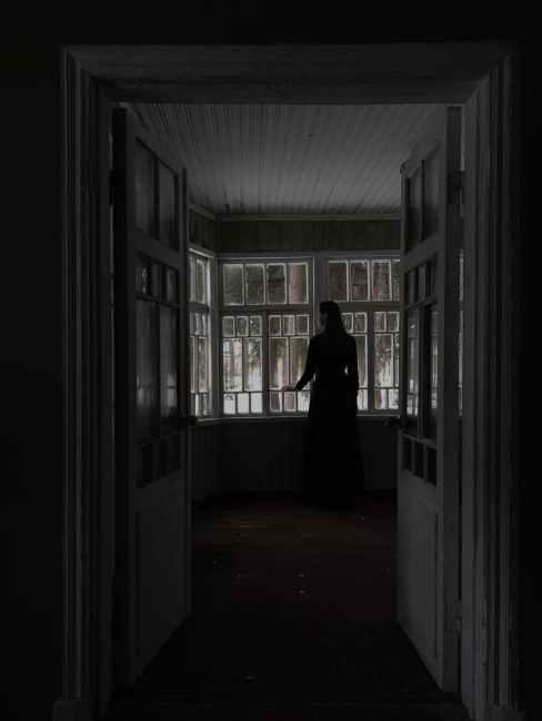 pensive female standing near window in dark room
