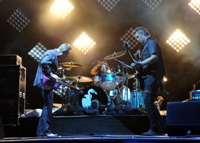 (L-R) John Paul Jones, Dave Grohl and Josh Homme of Them Crooked Vultures onstage. Image via  NME