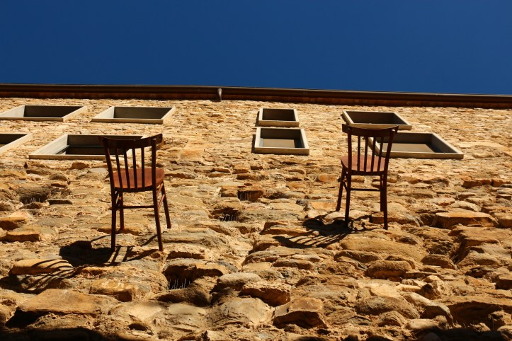 Besalu street art - two chairs on the wall, representing the daily human struggles we overcome
