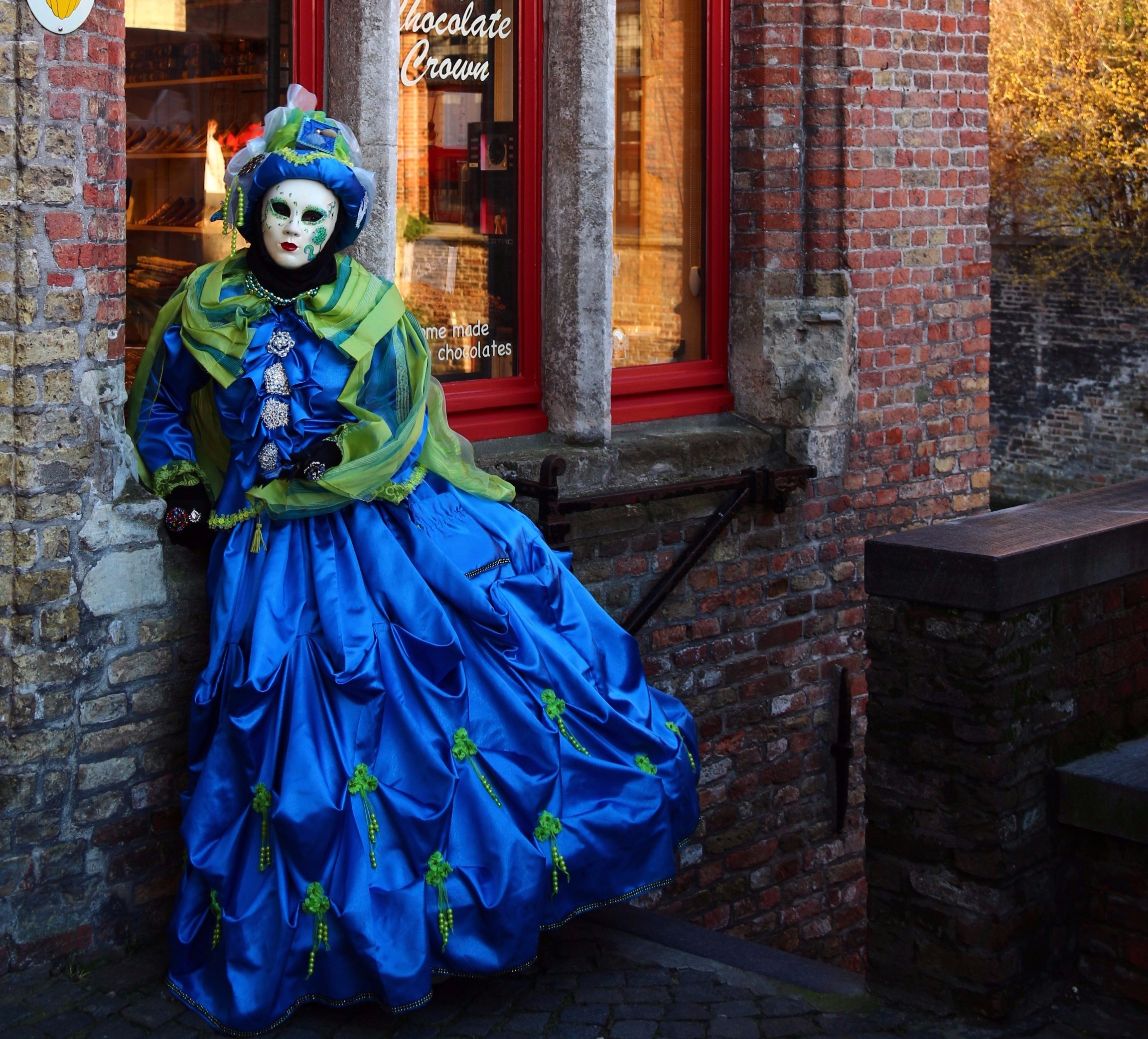 Venetian costumes in Bruges. A masked performer wearing a blue venetian  costume is posing in