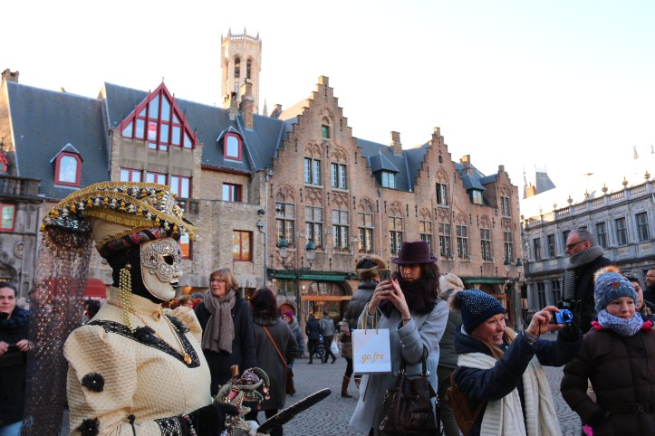 A woman wearing a venetial mask and costume is posing in bruges old market square