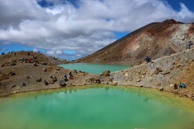 people taking a break on the shores of Emerald lakes on Tongariro alpine crossing,