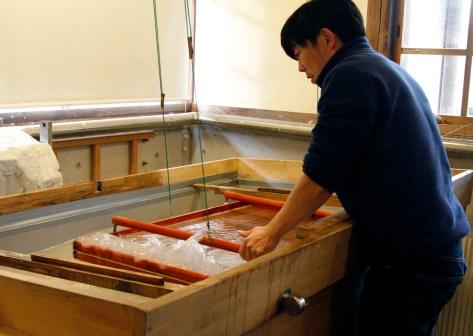 Osamu gently agitates the suketa to create his sheet of Usu Gami.