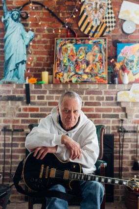 Russell Stone poses in front of some paintings by his brother Matt Stone in Annapolis, Maryland.