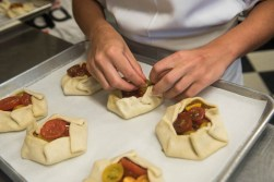 Baker Stephanie Squires prepares pastries with tomatoes and cheese at Bakers and Co. in Eastport. Photo by Alison Harbaugh