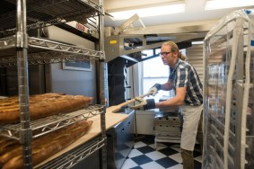 Bakers and Co. owner and baker, Chris Simmons, takes a batch of freshly made baguettes out of the oven during the morning bakery shuffle as he prepares the morning breads and pastries. Photo by Alison Harbaugh