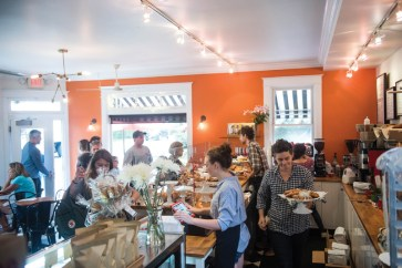 A busy Friday morning at Bakers and Co. in Eastport. Customers come in for fresh baked breads, pastries, soups and coffee and tea drinks. If needed...behind the counter: Hannah Hall, Emily Tahaburt, Joel Bourland & owner Lucy Montgomery (with tray) Photo by Alison Harbaugh