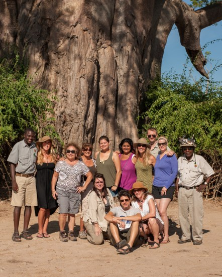 Nonprofit Dazzle Africa philanthropic safari group photo taken in front of giant baobab tree, South Luangwa National Park, Zambia.