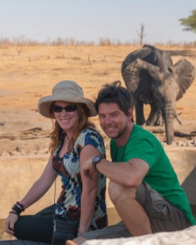 Mike and Nancy having fun posing in front of an elephant in Zimbabwe.