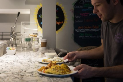 Server Philip Miles gathers hot breakfast to serve to customers at Evelyn's on October 8, 2018.