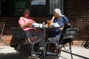 Sisters Chris Burnett (left) and Sally Johnson visit over lunch on the patio at Evelyn's on September 26, 2018.