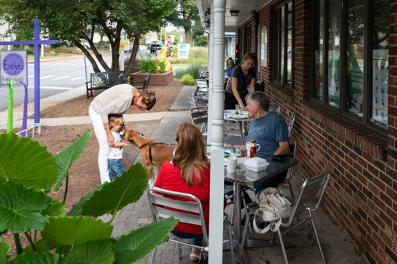 Customers visit after breakfast on the patio at Evelyn's on a Monday morning.