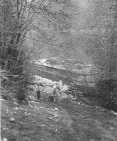 Off loading pipe for the waterline from a barge and then being carried up the hill by horse and stone boat. photo credit - Fred Heddle