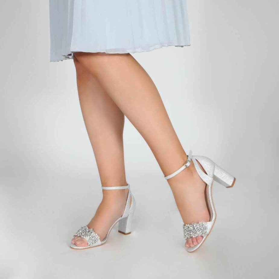 Model wearing Perfect Bridal silver sparkle shoes with block heel and ankle strap