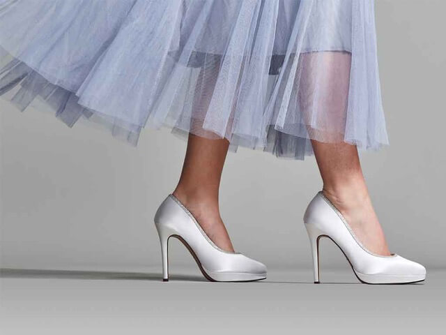 Rainbow Club Tallulah ivory bridal shoe. Features an almond-shaped toe, elegant stiletto heel and a platform sole. Finished with a silver shimmer trim which curves around the foot offering just a hint of sparkle