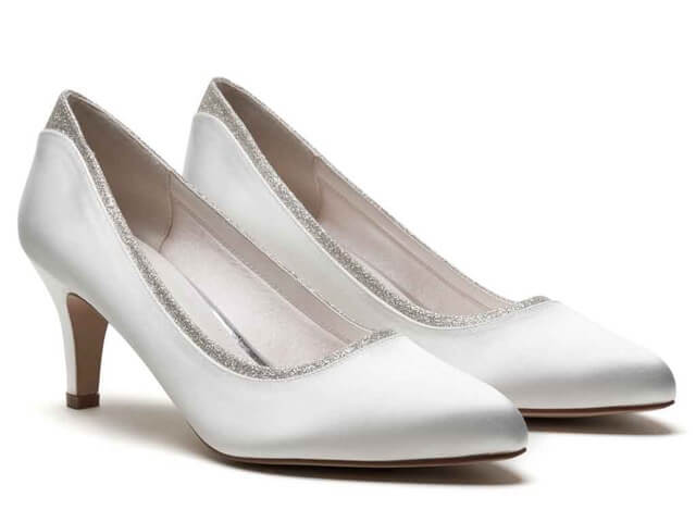 Rainbow Club Jara ivory satin bridal shoes. They have a round toe, slender mid-height heel and are finished with a silver shimmer trim offering just a hint of sparkle