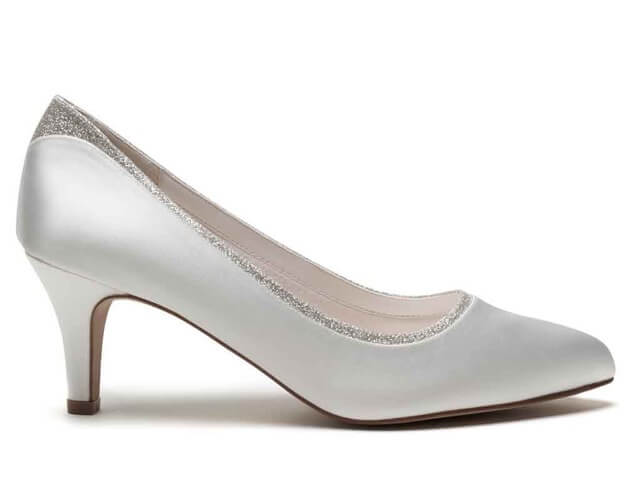 Rainbow Club Jara ivory satin bridal shoe. Has a round toe, slender mid-height heel and is finished with a silver shimmer trim offering just a hint of sparkle