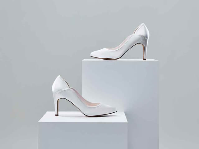 Rainbow Club Lucy ivory satin bridal shoe. These shoes feature a softly-pointed toe, slim, mid-height heel and are finished with a beautifully-curved silhouette trimmed with overlay satin
