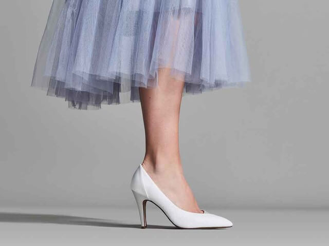 Rainbow Club Roux bridal shoe. Crafted from ivory satin on the heel and Italian ivory fine shimmer on the rest of the shoe. They have a soft pointed toe, open waist cut and a stiletto heel