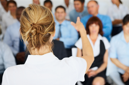 Rear view of a female spokesperson giving a presentation to her colleagues